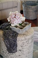 Hydrangea flower in wooden crate and black, sequined fabric on cylindrical pouffe