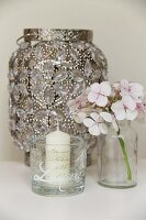 Candle in glass with pattern of lettering, hydrangea flower and antique lantern decorated with crystals