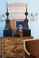 Partially visible chair in front of chest with marquetry and art objects in front of pictures of blue-painted wall