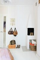 Handbags hanging on wall hooks next to open corner fireplace in bedroom