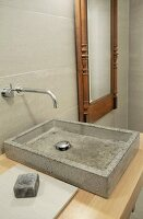 Concrete sink on wooden counter and designer wall-mounted tap fitting next to mirror with antique wooden frame