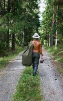 Woman wearing smart, traditional country-style clothing walking along woodland path with duffle bag over shoulder