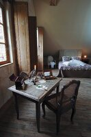 Old table and cane chair as small writing desk set in vintage-style bedroom