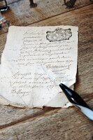 Old, crumpled document and glass quill pen on antique, natural wood table