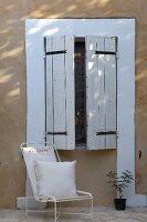 Cushion on delicate, white metal chair against house facade below window with closed, white wooden shutters