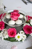 Rose and floating candles in bowl of water surrounded by wreath of roses and ox-eye daisies