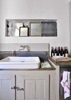 Collection of mirrors in niche above vintage sink on grey base unit in simple interior