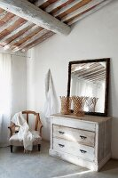 Mirror on vintage chest of drawers and armchair below Mediterranean roof structure on corner of bedroom
