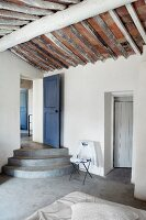 Concrete steps leading to blue wooden door and rustic exposed roof structure in purist bedroom