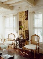 Side table in front of ethnic wall hanging and antique chairs in front of windows with louver blinds