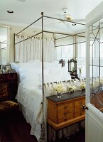 View through open door of four-poster bed with metal frame; vases of flowers on antique chest of drawers at foot of bed