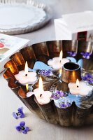 Bundt tin filled with water, floating candles & viola flowers
