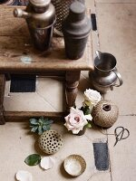 Wooden tables with nostalgic cocktail shakers, pewter tankards, ball of twine, scissors, roses and succulents on a stone floor