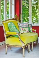 Antique Louis XVI sofa with yellow velvet cover and patterned scatter cushions below windows in corner with red-painted walls