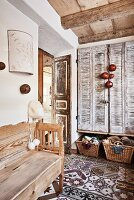 Hallway with rustic wooden bench on patterned tiled floor and vintage-style interior shutters