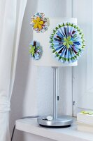 Colourful paper flowers decorating lampshade