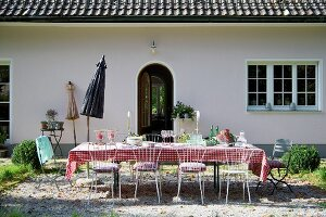 Set table and delicate metal chairs on gravel terrace in garden adjoining rustic house