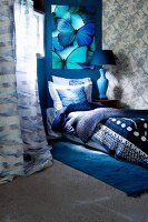 Bed with blankets, pillows and scatter cushions in shades of blue below picture of bright turquoise and blue butterflies