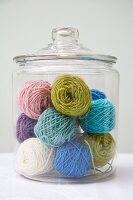 Balls of wool of various colours in glass jar