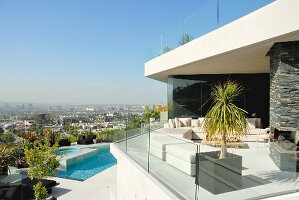 Contemporary house with white outdoor furniture on terrace with glass balustrade; pool and urban panorama in background