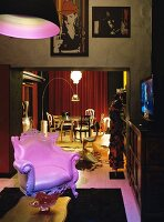 Neo-baroque leather armchair illuminated by pink light; gilt dining table and various chairs in background