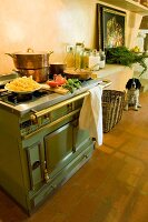 Copper pans on matt green, vintage cooker with brass rail in Tuscan kitchen-dining room