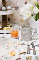 Napkin and tablecloth with colourful hen pattern and grey mug with hen-motif relief on table set for Easter