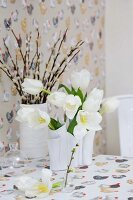 Vases of white tulips and pussy willow on tablecloth with Easter pattern of hens