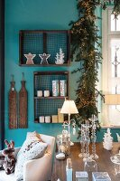Glass candle sticks, table lamp and candle lanterns on table in front of Christmas decorations in wooden display case and garland of fir branches and fairy lights on turquoise wall