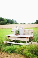 Two milk churns on wooden bench on edge of meadow