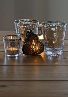Lit tealights in Oriental tea glasses and heart-shaped ornament on wooden surface