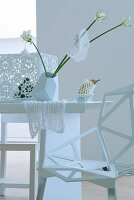 Arrangement of white flowers and doilies on white table in white room