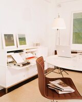 White study with storage space in sideboard; swivel chair and laptop on round table