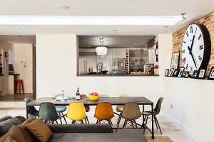 View into raised kitchen from dining area; skylight above long table and designer chairs of different colours