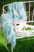 Small portable radio on seat cushion and checked woollen blanket on delicate, white, metal garden bench outdoors