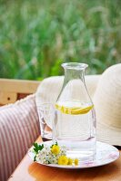 Carafe filled with water and slices of lemon and wild flowers on plate in front of straw hat on wooden surface