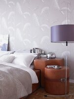 Detail of double bed with fitted, custom-made group of bedside cabinets covered in brown leather against wall with pale grey patterned wallpaper; standard lamp with purple lampshade in foreground