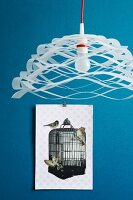 Airy, paper pendant lamp in front of collage of cut-out paper birds and birdcage on blue wall
