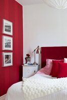 Framed pictures on red striped wall, bed with red headboard and retro-style lamp on bedside table