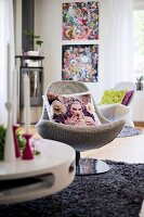 Scatter cushions on swivel easy chair on grey, long-pile rug in modern interior