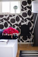Pink, flower-shaped cushion on white sideboard in front of wall with black and white floral wallpaper