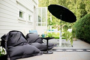 Black beanbags and side table in front of table under black parasol on terrace in sunny garden