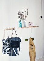 Still-life cloakroom arrangement with ceramic vases on wall-mounted shelf, collection of bags on hooks and vintage skateboard