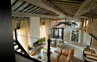 View from mezzanine into living space with armchairs, dining area and wood-beamed ceiling in renovated country house with Mediterranean, loft-style ambiance