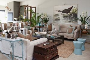 Living room with sand-coloured sofa set and pale blue stools around coffee table in front of picture of aquatic bird
