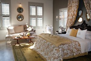 Double bed with canopy over headboard in elegant, country-house style bedroom with closed shutters on windows