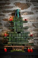 Stylised Christmas tree made from stacked, green antiquarian books with red candles
