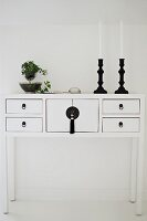 Black candlesticks and ivy on white lowboy cabinet against wall