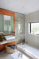 Glass partition between tiled shower area with window and washstand with countertop sink