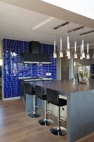 Bar stools with black leather covers at grey kitchen island below several rows of pendant lamps; wall of indigo tiles in background